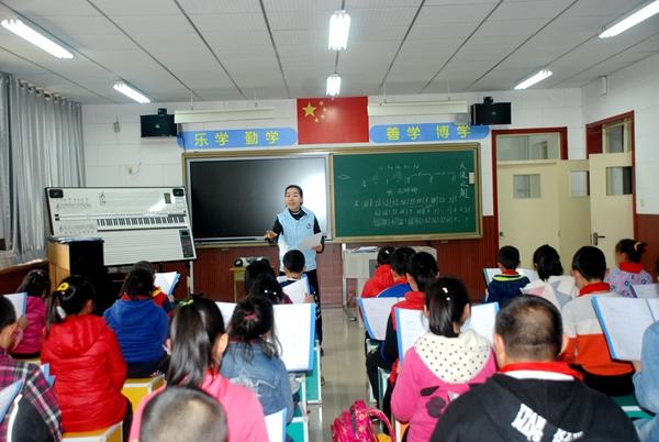 图4 甘益聪为外来务工子女学生进行声乐辅导.JPG