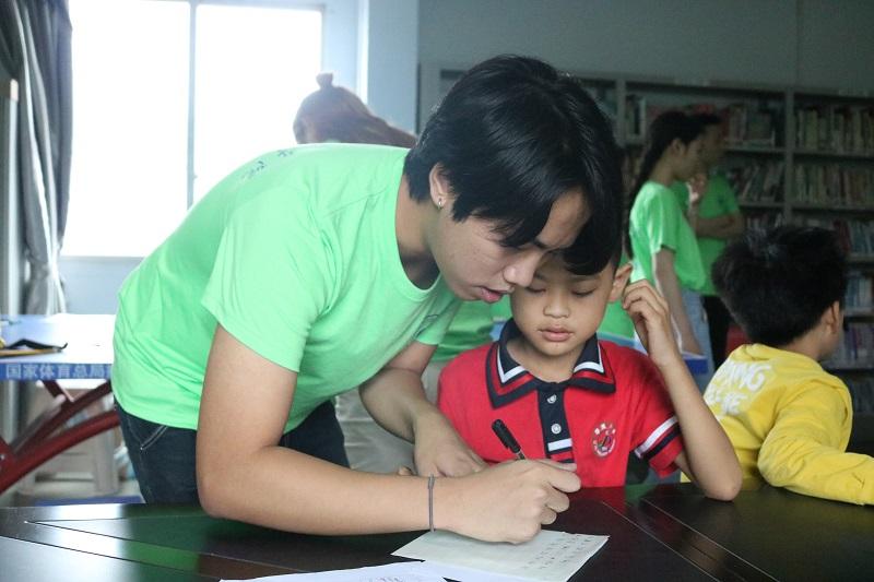志愿者在教小朋友.JPG