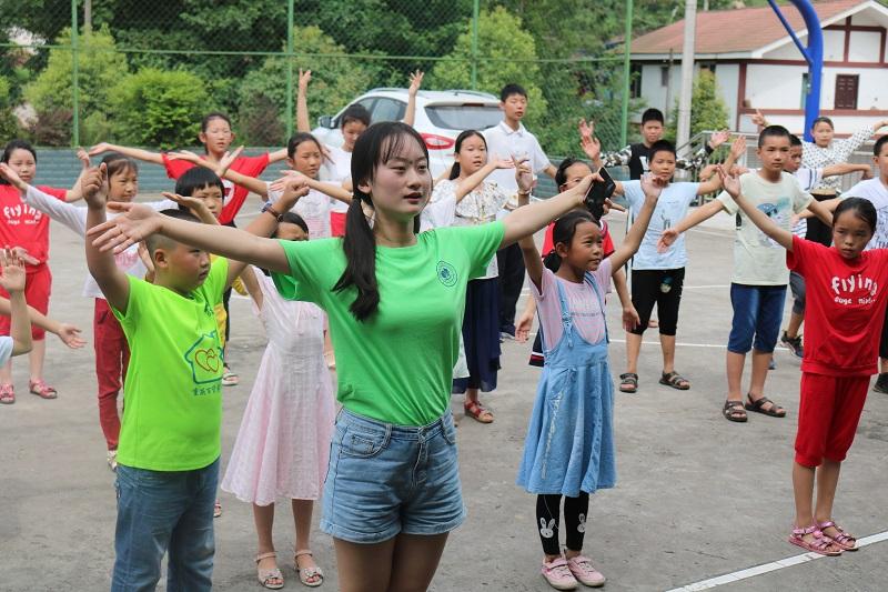 志愿者在教小朋友们跳舞.JPG