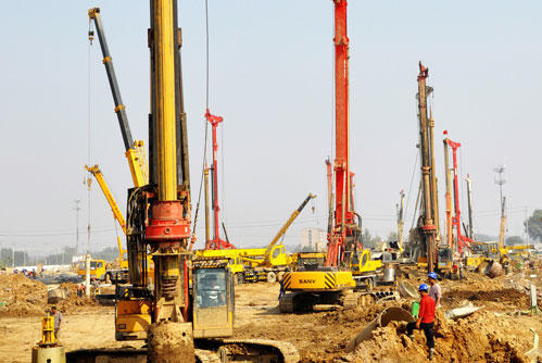 旋挖钻是一种合适建筑基础工程项目中成孔工作的工程施工机械装置。关键适合碎石土、黏性土、粉质土等施工,在钻孔灌注桩、连续墙、基础加固等多种多样地基与基础施工现场得到广泛应用,旋挖钻的最大功率大约为125~455kW,驱动力輸出扭距为120~405kN·m,*大德孔直?酱锏�1.5~2m,*大德孔深层为60~90m,能够考虑这些大中型基础项目施工的要求。  此类钻探机一般使用液压机履带伸缩式汽车车身、自主起降折叠式钻桅、伸缩节钻具、含有平整度自动检测控制、深度数码显示信息等,整个机械调节通常使用液压机插装式操纵、负载感测器,具备实际操作轻巧、舒服等特点。主、副2个卷扬机可适用施工工地多种多样状况的需要。此类钻探机相互配合不一样钻探设备,适用干试(短螺旋式)或湿试(旋转斗)及地层层(岩样钻)的成桩工作,还能配挂长螺旋式钻、地下连续墙闸门启闭机、震动桩锤等,完成多种多样作用,关键用以市政管理、道路隧道桥梁、工业制造和农业建筑、地下连续墙、水利工程、防水层桥面防护等基础项目施工。中国的权威专家认为:旋挖钻在中国将来两年仍有相当大的销售行业。  旋挖钻的机械装置系统关键包括起升组织、船头、主、辅卷扬机、回转工作台、转向头灯架、冲压组件、钻具、钻探装置等。选用了垂直四边形起升组织、自主起飞可折叠船头;自动控制系统检验服务器输出功率、旋转精准定位及安全性维护:自动检测、调节钻具的平整度:打孔深层预设和测试等新技术应用。五颜六色显示器形象化显示信息工作中情况参数,整个机械调节上使用插装式操纵、负载感测器,最大限度地提高 了实际操作的便捷性、协调性和安全性舒适度,充足完成了人、机、液、电一体化。  旋挖钻所配套设备的短螺旋式麻花钻、一般麻花钻、捞沙麻花钻、岩样等钻探设备,可钻入黏土层、砂砾层、河卵石层与立风化层砂岩等不一样地质学。  旋挖钻钻入成桩加工工艺及基本原理。旋挖成桩首先是按照钻探机已有的走动作用跟船头起升组织推动钻探设施可迅速到达桩位,运用船头导向性下发钻具将底端含有悬板的桶式麻花钻置放进孔距,钻探机回转工作台设备为钻具出示扭矩、设备按照充压回转工作台的方式将加压力传送给钻具、麻花钻,麻花钻旋转粉碎岩土工程,并立即将其装进麻花钻内,随后又由钻探机提高系统和伸缩节钻具将麻花钻明确指出孔外卸土,那样周而复始,不断采土、卸土,直到钻至设计计划深层。对粘结力好的岩土壤层,可使用干试或清水钻入生产工艺。而在松软易脱落地质结构,则必须使用静态数据泥浆护壁成孔钻入制作工艺。  旋挖钻钻入加工工艺与正反面循环系统钻入生产工艺的牙根差别是,前面一种是利用麻花钻将粉碎的岩土工程随即从孔内取下,而中间一种是通过砂浆循环系统向孔外清理钻渣。